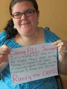 "Young caucasian woman with curly brown hair off to the side wearing purple glasses and a turquoise floral-patterned shirt. She is holding up a sign written in pink and green ink on white paper that reads: ""Calling all senators: It's time for the U.S. to take their seat at the table in support of global disability rights! Please be the example I know we can be! Ratify the CRPD!"""